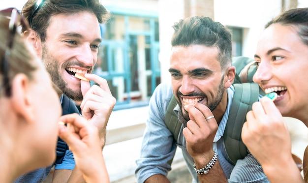 Glückliche tausendjährige freunde, die spaß im stadtzentrum isst zuckersüßigkeiten haben
