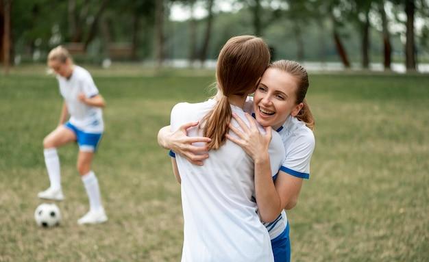 Glückliche teamspieler umarmen sich