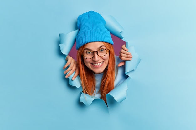 Glückliche teenager-mädchen bricht durch papierwand hat spaß sieht trägt gerne blaue hut brille lächelt zahnlos