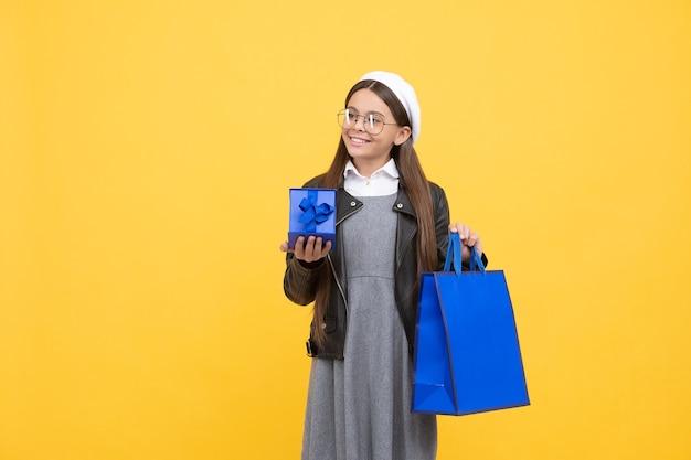 Glückliche teenager-mädchen zurück zur schule mit geschenkbox und einkaufstasche gelben hintergrund kopie raum, vorhanden.