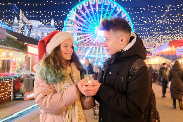 Glückliche teenager paar jungen und mädchen in der weihnachtsmütze am weihnachtsmarkt, der hände mit kerze wärmt