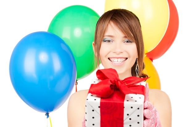 Glückliche teenager-partygirl mit luftballons und geschenkbox