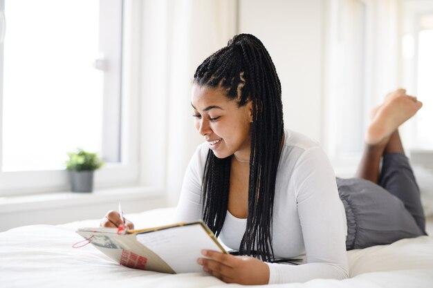 Glückliche teenager-studentin, die zu hause auf dem bett liegt, ein buch liest und notizen macht