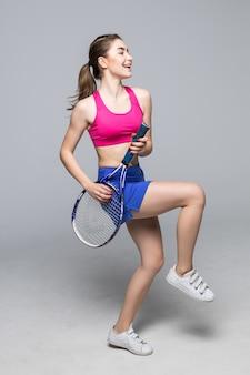 Glückliche tennisspielerin, die auf schläger spielt, wie auf gitarre isoliert