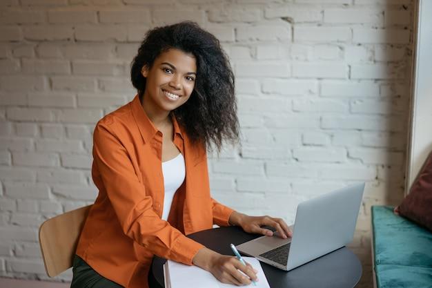 Glückliche texterin, die freiberuflich von zu hause aus arbeitet. geschäftsfrau mit laptop, planung startup