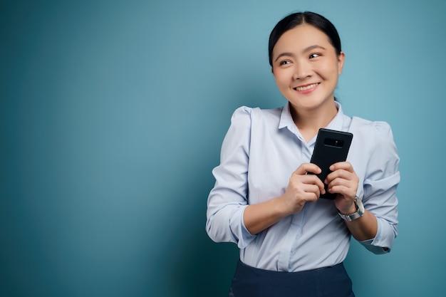 Glückliche tippnachricht der asiatischen frau mit lokalisiertem smartphone auf.