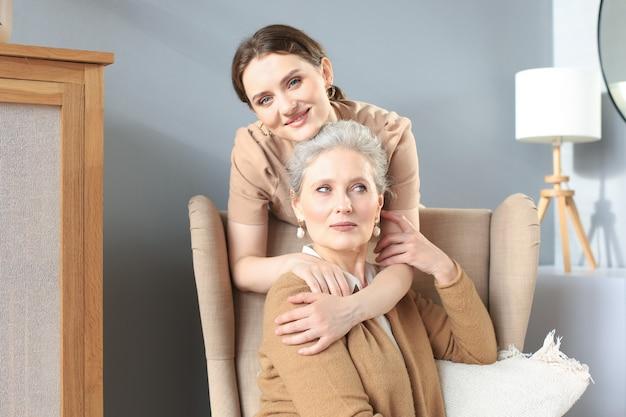 Glückliche tochter, die ältere mutter umarmt, hinter dem stuhl im wohnzimmer steht und den zarten moment zu hause genießt