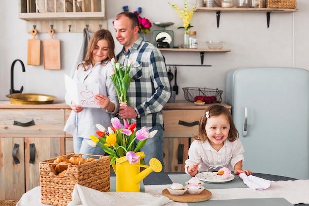Glückliche tochter, die kleinen kuchen nahe eltern mit grußkarte macht