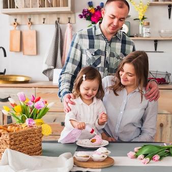 Glückliche tochter mit den eltern, die kleinen kuchen in der küche machen