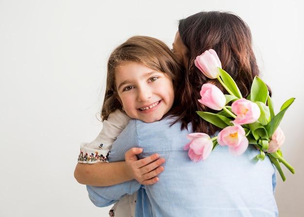 Glückliche tochter mit den tulpen, die mutter umarmen