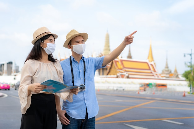 Glückliche touristen des asiatischen paares, die maske tragen
