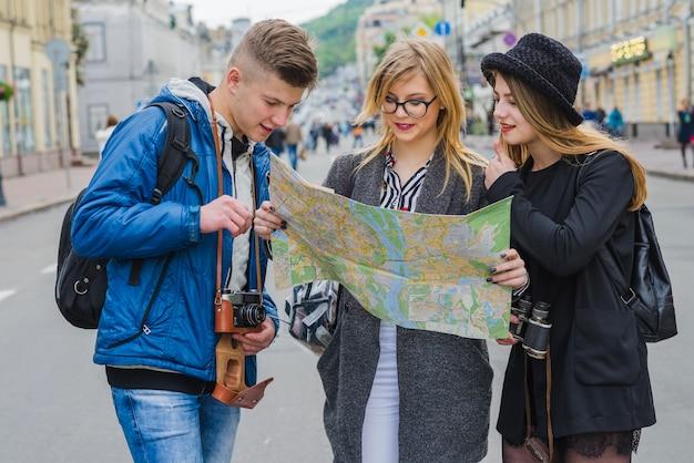 Glückliche touristen, die mit karte navigieren