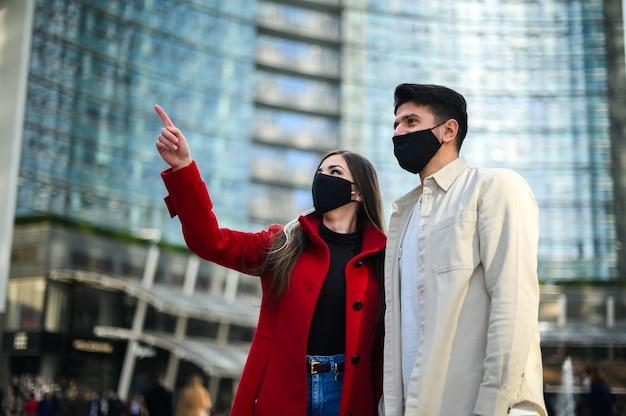 Glückliche touristen mit covid- oder coronavirus-masken paaren zusammen in einer stadt und sehen einen interessanten ort