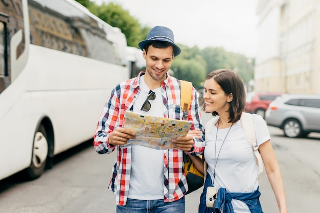 Glückliche touristen oder reisende, die mit glücklichem ausdruck in der karte suchen, froh sind, einen weiteren zu erreichenden ort zu sehen, gute laune nach einer wundervollen busreise zu haben, sightseeing zu machen, eine reise zusammen zu unternehmen