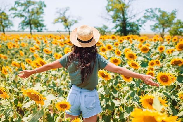 Glückliche touristenfrau im hut, der im sommertag auf dem gebiet der sonnenblumen geht