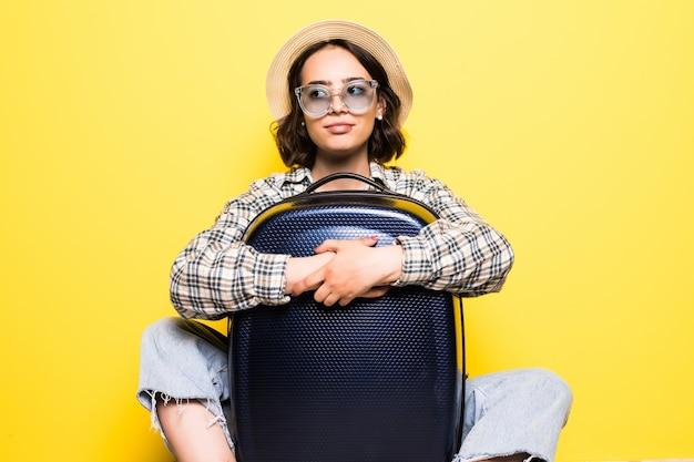 Glückliche touristenfrau in legerer sommerkleidung, hut sitzt mit koffer und sieht beiseite isoliert auf gelb-orangefarbener wand. mädchen, das ins ausland reist, um am wochenende zu reisen. flugkonzept