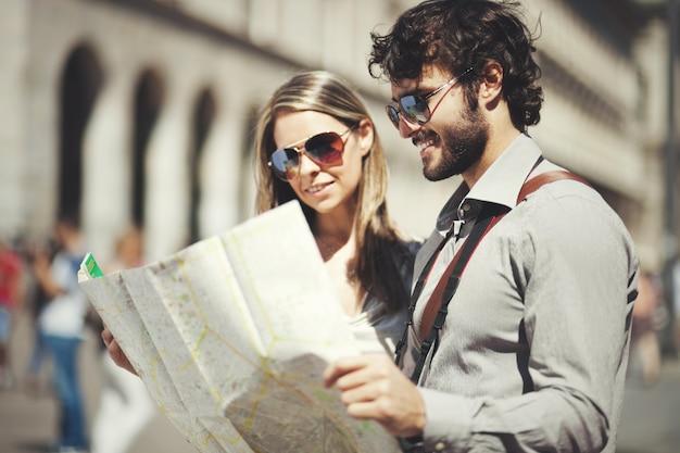 Glückliche touristenpaare, die karte halten