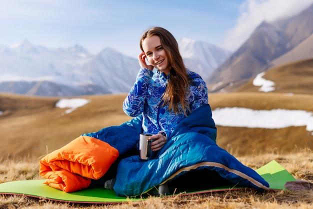 Glückliche touristin sitzt auf dem hintergrund der berge und trinkt tee