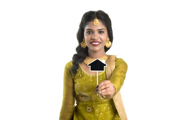 Glückliche traditionelle indische junge frau, die ein kleines hausausschnittbrett in ihren händen auf einem weißen hintergrund hält.