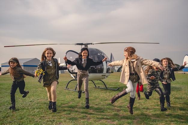 Glückliche tweenager-mädchen, die auf dem flugplatz laufen, nachdem sie im hubschrauber geflogen sind