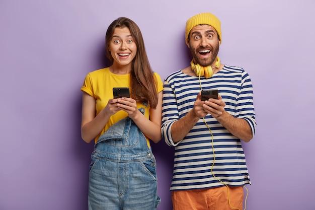 Glückliche überglückliche junge leute senden textnachrichten, die von modernen technologien abhängig sind