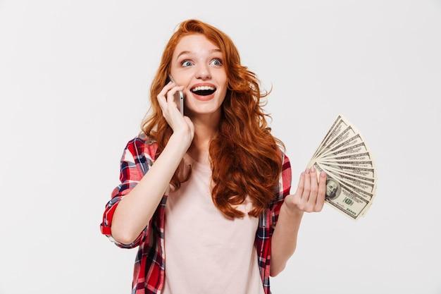 Glückliche überraschte ingwerfrau im hemd, die durch smartphone spricht, während sie geld hält und wegschaut
