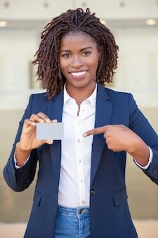 Glückliche überzeugte geschäftsfrau, die ausweis zeigt