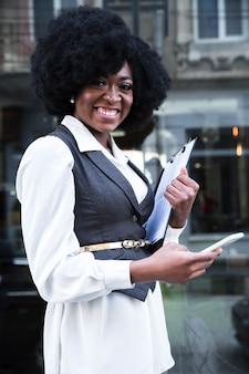 Glückliche überzeugte junge afrikanische geschäftsfrau, die handy verwendet