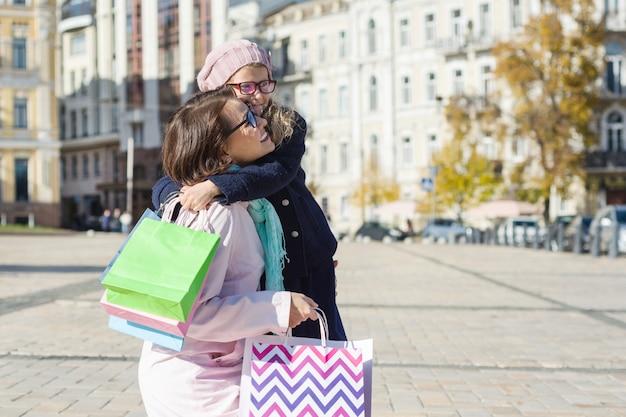 Glückliche umarmende mutter und tochter, mit einkaufstaschen