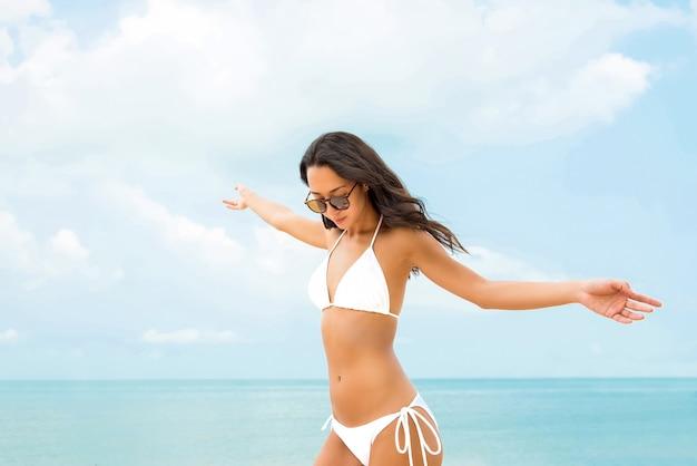 Glückliche unabhängige asiatische frau im weißen badeanzug am strand im sommer