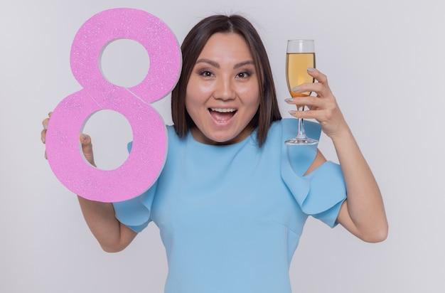 Glückliche und aufgeregte asiatische frau, die nummer acht und ein glas champagner hält