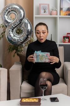 Glückliche und aufgeregte asiatische junge frau im schwarzen kleid, das auf einem stuhl mit der nummer acht geformtem ballon hält, das geschenk betrachtet, das es im hellen wohnzimmer betrachtet, das internationalen frauentag feiert