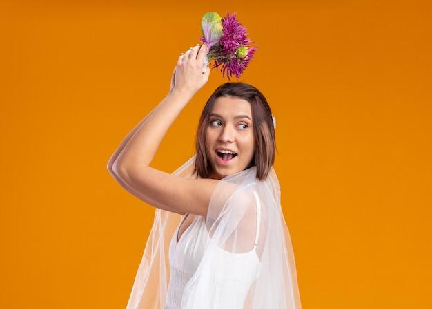 Glückliche und aufgeregte braut im schönen hochzeitskleid, die hochzeitsblumenstrauß werfen wird