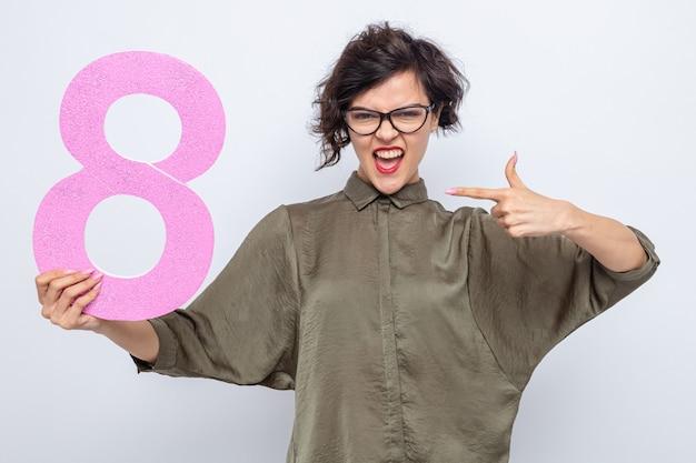 Glückliche und aufgeregte frau mit kurzen haaren, die die nummer acht aus pappe hält und mit dem zeigefinger darauf zeigt, um den internationalen frauentag 8. märz zu feiern, der auf weißem hintergrund steht