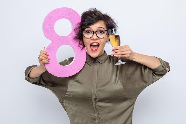 Glückliche und aufgeregte frau mit kurzen haaren, die nummer acht hält, hergestellt aus pappe und einem glas champagner lächelnd, das fröhlich internationalen frauentag 8. märz feiert