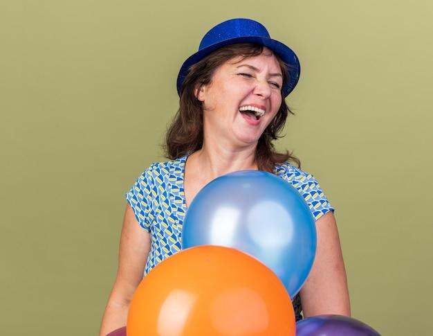 Glückliche und aufgeregte frau mittleren alters im partyhut mit einem haufen bunter luftballons, die heraus lachen