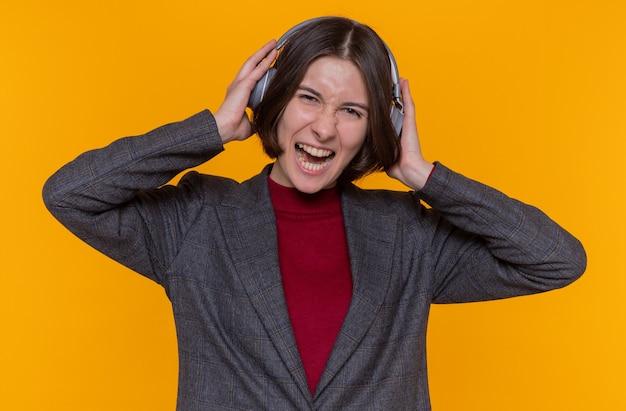 Glückliche und aufgeregte junge frau mit kurzen haaren, die graue jacke mit kopfhörern trägt und ihre lieblingsmusik genießt, die fröhlich über orange wand stehend lächelt