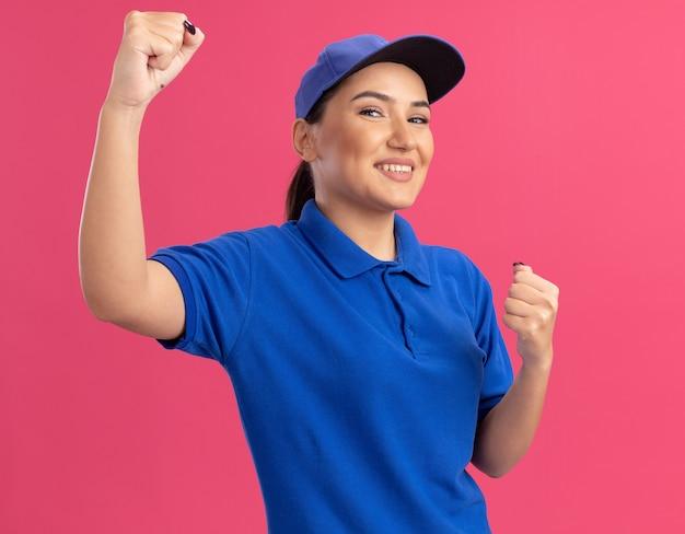 Glückliche und aufgeregte junge lieferfrau in der blauen uniform und in den geballten fäusten der kappe, die über rosa wand stehen