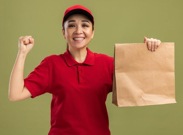 Glückliche und aufgeregte junge lieferfrau in roter uniform und mütze, die ein papierpaket mit einem lächeln auf dem gesicht hält und die faust über der grünen wand steht