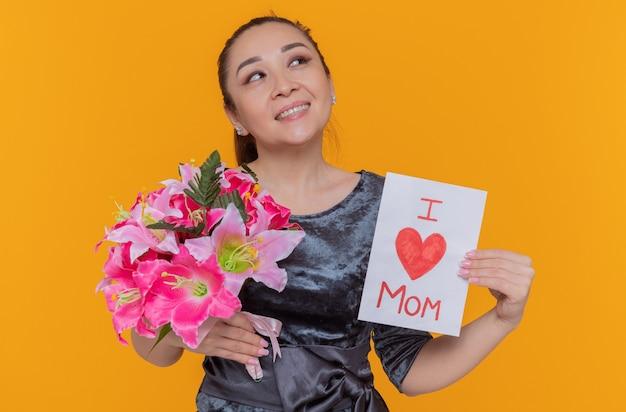 Glückliche und fröhliche asiatische frauenmutter, die grußkarte und blumenstrauß hält, der muttertag feiert und fröhlich über orange wand stehend lächelt