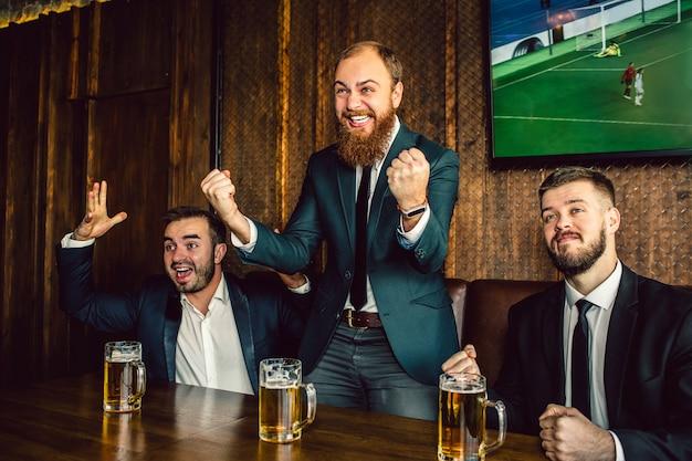 Glückliche und fröhliche junge männer sitzen und stehen in der bar. sie schauen fußballspiel. guy hat bierkrüge am tisch.