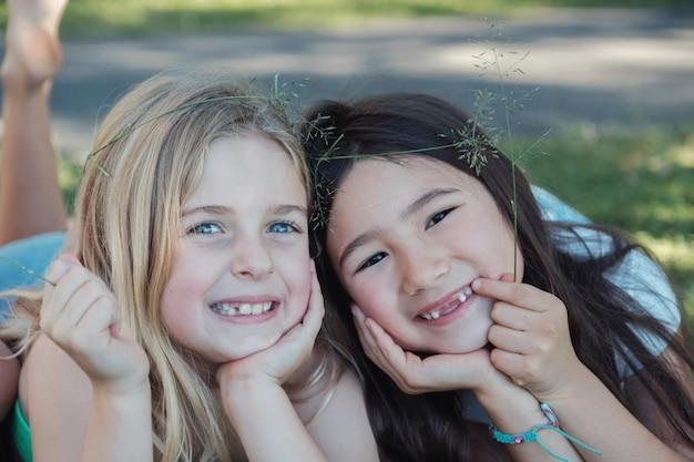 Glückliche und gesunde gemischte ethnische junge kleine mädchen, die im park, in den besten freunden und in der freundschaft lächeln