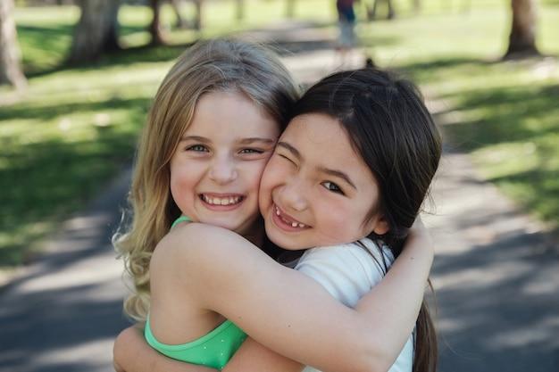 Glückliche und gesunde gemischte ethnische junge kleine mädchen, die im park, in den besten freunden und in der freundschaft umarmen und lächeln
