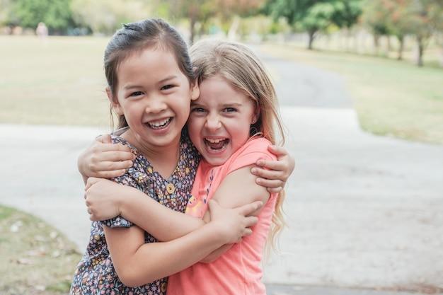 Glückliche und gesunde junge mädchen der gemischten rasse, die im park umarmen und lächeln, bester freund kinder und kinderfreundschaftskonzept