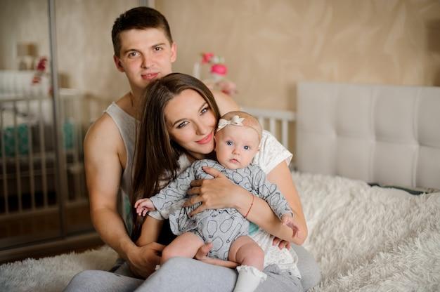 Glückliche und junge mutter mit dem vater, der sorgfältig neugeborenes baby hält