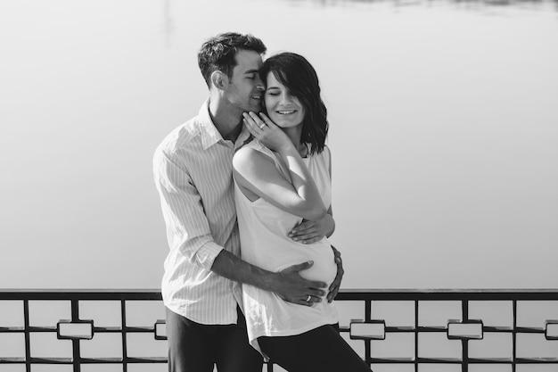 Glückliche und junge schwangere paare, die in der natur am see umarmen