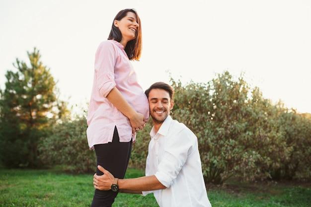 Glückliche und junge schwangere paare