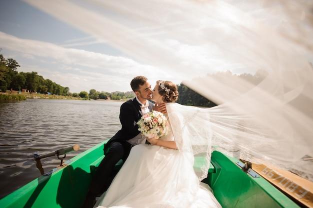 Glückliche und lächelnde braut mit dem bräutigam, der im boot küsst