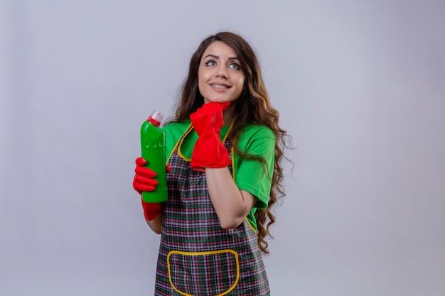 Glückliche und nachdenkliche junge schöne frau mit dem langen gewellten haar, das schürze und gummihandschuhe trägt, die mit der hand auf kinn stehen, während flasche des reinigungsmittels halten wegsehen stehen
