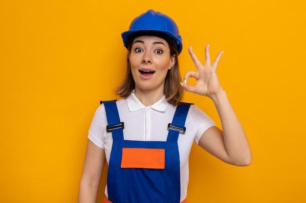 Glückliche und positive junge baumeisterin in bauuniform und schutzhelm, die lächelnd aussieht und ein gutes zeichen tut